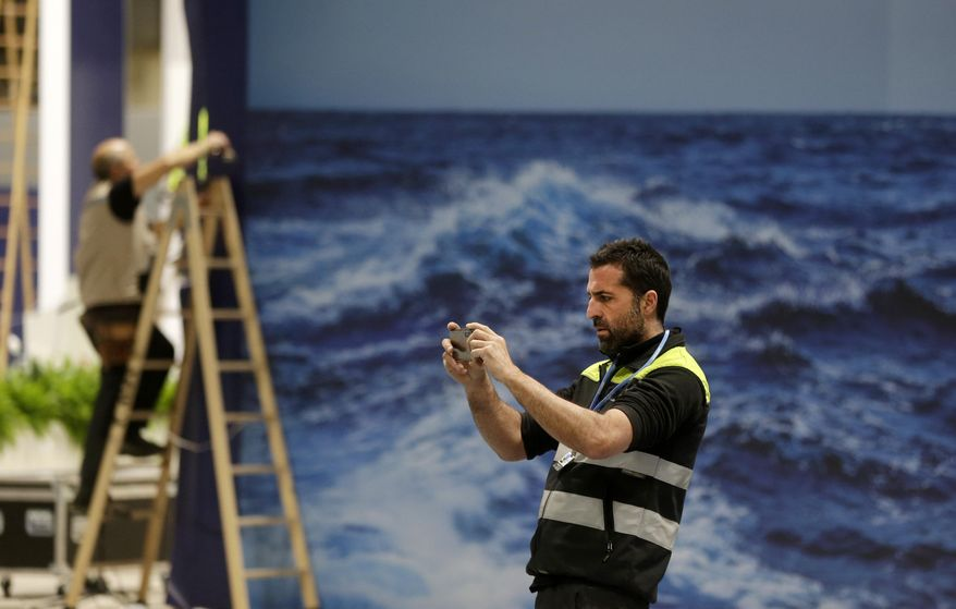 A worker takes a photograph while stands are being set up for the COP25 Climate summit in Madrid, Spain, Sunday, Dec. 1, 2019. This year's international talks on tackling climate change were meant to be a walk in the park compared to previous instalments. But with scientists issuing dire warnings about the pace of global warming and the need to urgently cut greenhouse gas emissions, officials are under pressure to finalize the rules of the 2015 Paris accord and send a signal to anxious voters. (AP Photo/Paul White)