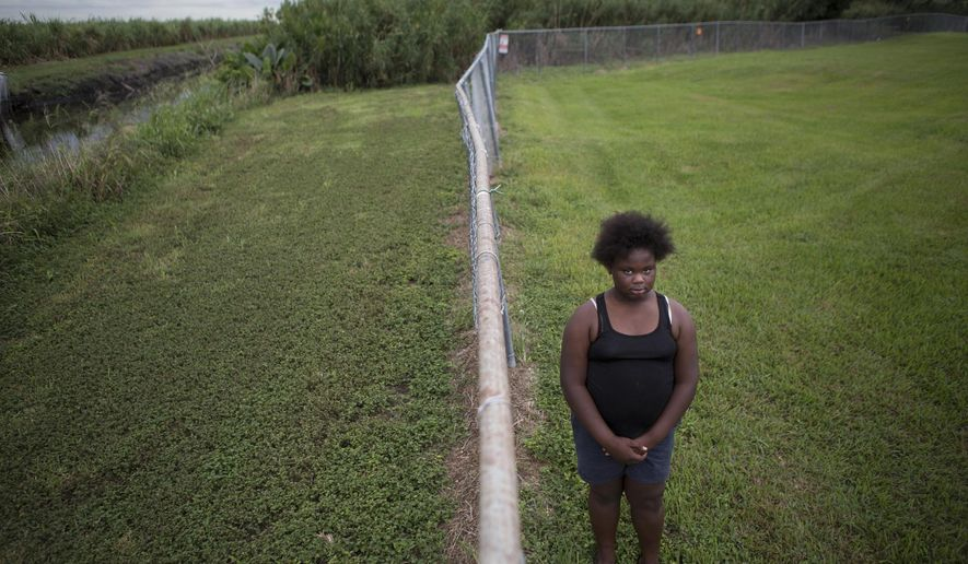 In this Nov. 4, 2019 photo, Kaniyah Patterson stands in front of a sugar cane field behind her home in Pahokee, Fla. Patterson says that smoke from sugar cane burns trigger her asthma. For generations, Florida's sugar cane farmers have legally set fire to their fields prior to harvest. But the smoke is a nuisance for predominantly poor communities near the fields. (AP Photo/Ellis Rua)