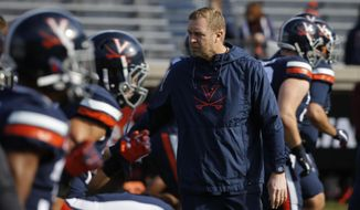 Virginia head coach Bronco Mendenhall watches his team warm up before an NCAA college football game against Virginia Tech in Charlottesville, Va., Friday, Nov. 29, 2019. (AP Photo/Steve Helber) **FILE**