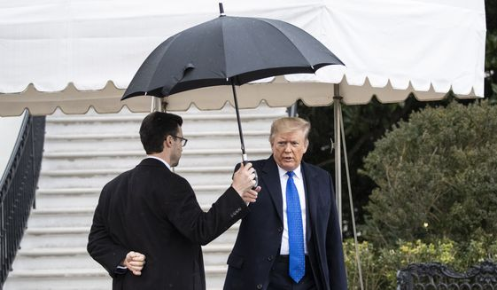 President Donald Trump takes an umbrella from an aide before speaking with reporters on the South Lawn of the White House before departing, Monday, Dec. 2, 2019, in Washington. (AP Photo/Alex Brandon)