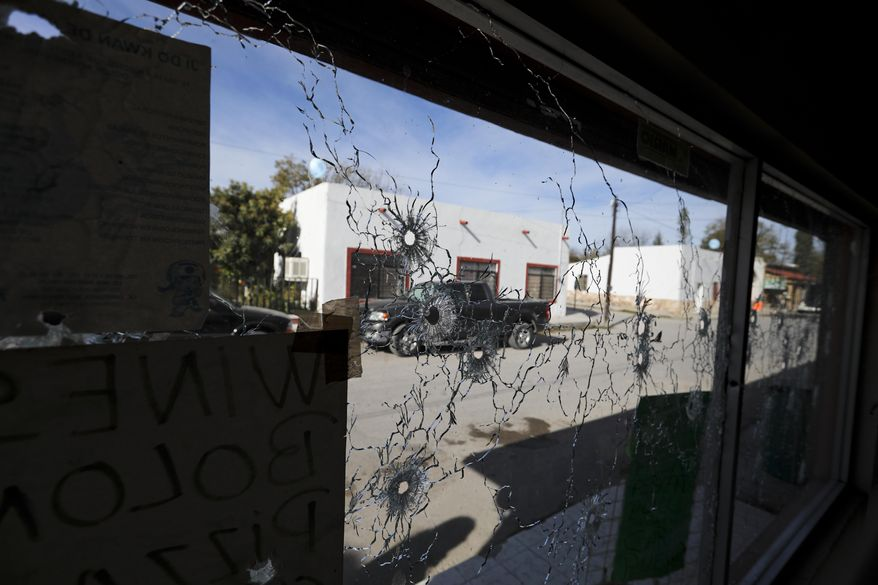 A shop's windows are riddled with bullet holes near City Hall after a gunbattle in Villa Union, Mexico, Monday, Dec. 2, 2019. The small town near the U.S.-Mexico border began cleaning up Monday even as fear persisted after 22 people were killed in a weekend gunbattle between a heavily armed drug cartel assault group and security forces. (AP Photo/Eduardo Verdugo)
