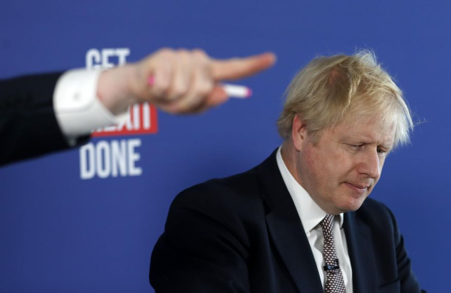 Chancellor of the Duchy of Lancaster Michael Gove, left, gestures during a media conference with Britain's Prime Minister Boris Johnson, right, in London, Friday, Nov. 29, 2019. Britain goes to the polls on Dec. 12. (AP Photo/Frank Augstein)