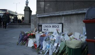 Tributes placed by the southern end of London Bridge in London, Monday, Dec. 2, 2019. London Bridge reopened to cars and pedestrians Monday, three days after a man previously convicted of terrorism offenses stabbed two people to death and injured three others before being shot dead by police. (AP Photo/Matt Dunham)