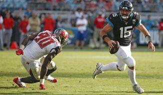 Jacksonville Jaguars quarterback Gardner Minshew (15) scrambles away from Tampa Bay Buccaneers linebacker Jason Pierre-Paul (90) during the second half of an NFL football game, Sunday Dec. 1, 2019, in Jacksonville, Fla. (AP Photo/Stephen B. Morton)