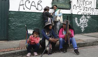Members of the Indigenous Guard wait for the start of a protest march against President Ivan Duque, in Bogota, Colombia, Friday, Nov. 29, 2019. The indigenous group arrived in the Colombian capital Friday to take part in the upcoming Dec. 4th national strike and anti-government march. (AP Photo/Fernando Vergara)