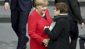 German Chancellor Angela Merkel, left, and Annegret Kramp-Karrenbauer, right, Defence Minister and chairwoman of the German Christian Democratic Union CDU, shake hands as they arrive for a meeting of the German federal parliament, Bundestag, at the Reichstag building in Berlin, Germany, Wednesday, Nov. 27, 2019. (AP Photo/Michael Sohn)