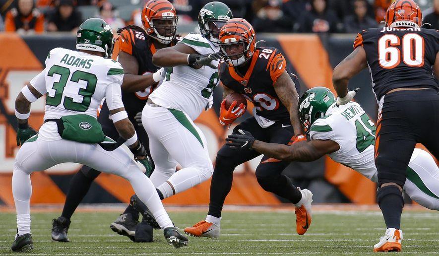 Cincinnati Bengals running back Joe Mixon (28) runs the ball against New York Jets outside linebacker Jordan Jenkins (48) and strong safety Jamal Adams (33) during the first half of an NFL football game, Sunday, Dec. 1, 2019, in Cincinnati. (AP Photo/Frank Victores)