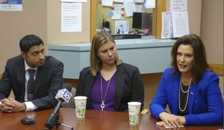Democratic Gov. Gretchen Whitmer, right, U.S. Rep. Elissa Slotkin, D-Mich., and Dr. Farhan Bhatti, CEO of Care Free Medical, speak at an event to encourage enrollment under the federal health care law on Monday, Dec. 2, 2019, at one of Care Free's clinics in Lansing, Mich. (AP Photo/David Eggert)