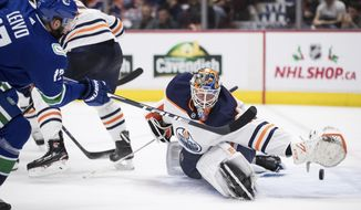 Vancouver Canucks' Josh Leivo, left, scores against Edmonton Oilers goalie Mikko Koskinen, of Finland, during the second period of an NHL hockey game, Sunday, Dec. 1, 2019, in Vancouver, British Columbia. (Darryl Dyck/The Canadian Press via AP)