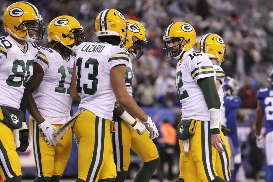 Green Bay Packers quarterback Aaron Rodgers, right, celebrates after throwing a touchdown to Davante Adams during the second half of an NFL football game against the New York Giants, Sunday, Dec. 1, 2019, in East Rutherford, N.J. (AP Photo/Adam Hunger)
