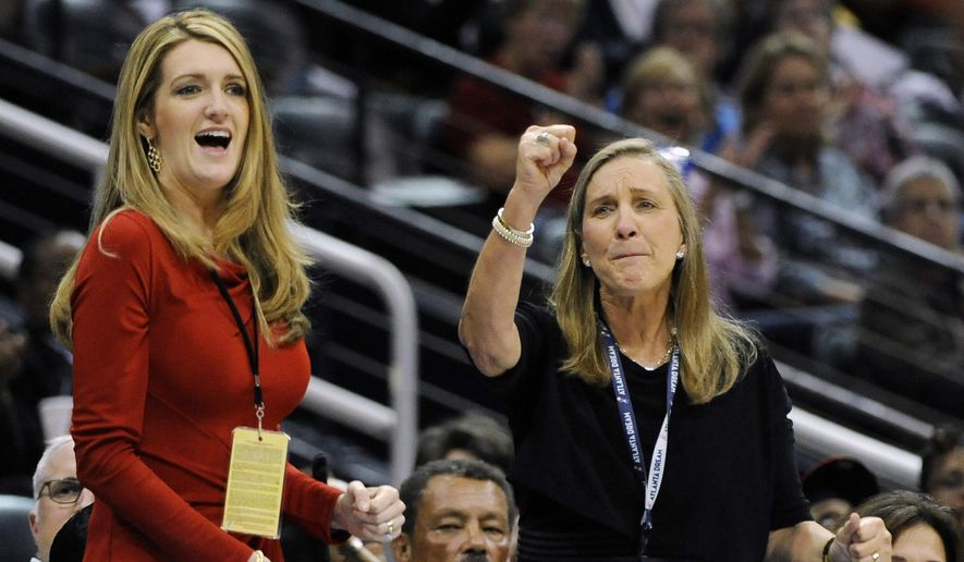 In this Tuesday, Sept. 6, 2011, file photo, Mary Brock, right, and Kelly Loeffler cheer from their courtside seats as the Atlanta Dream basketball team plays in the second half of their WNBA basketball game, in Atlanta. (AP Photo/David Tulis, File)