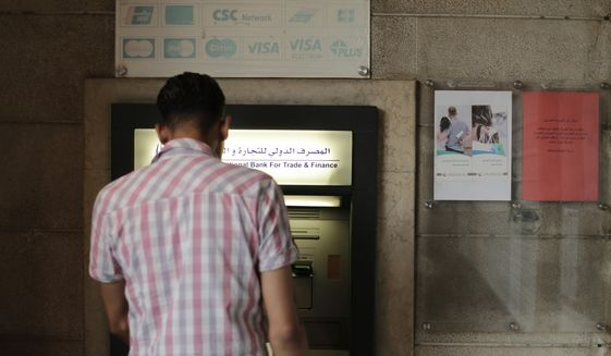 FILE - In this July 24, 2019 file photo, a man stands in front of an ATM machine outside a branch of the International Bank for Trade and Finance, in Damascus, Syria. The Syrian pound has hit a record low amid the country's grinding war and as a financial and political crisis roils neighboring Lebanon, Syria's economic lung. The dollar was worth 920 Syrian pounds at some exchange shops on Monday, Dec. 2, 2019, in the capital, Damascus, a sharp drop from recent days. (AP Photo/Hassan Ammar, File)