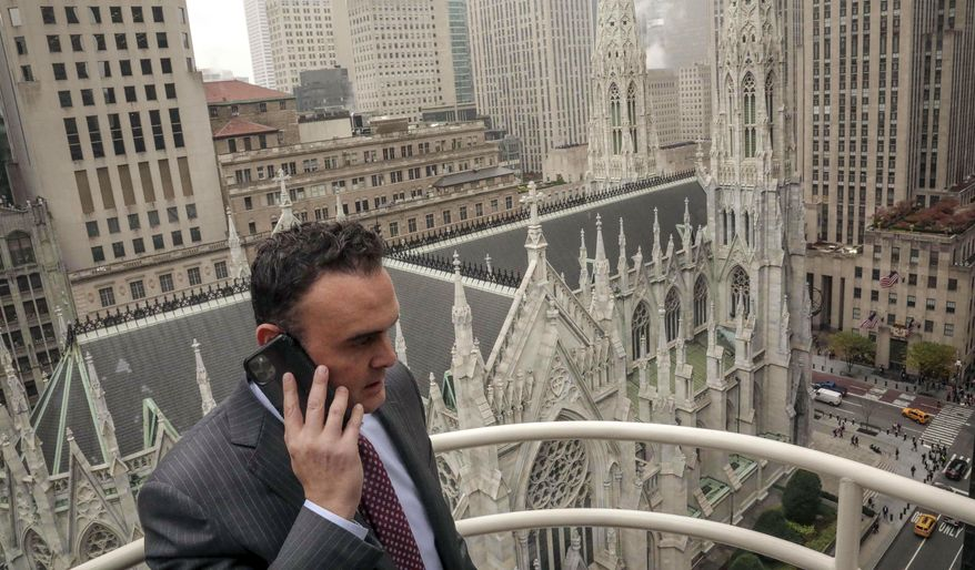 In this Tuesday, Oct. 29, 2019, photo, attorney Adam Slater takes a phone call on a patio outside his high-rise Manhattan office overlooking St. Patrick's Cathedral, in New York. Slater's firm is representing clients accusing the Roman Catholic Church of sexual abuse, a clientele that is rapidly growing after New York state opened its one-year window allowing sex abuse suits with no statute of limitations. (AP Photo/Bebeto Matthews) ** FILE **