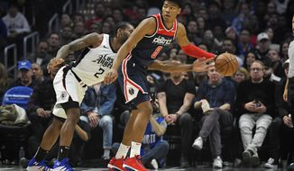 Los Angeles Clippers forward Kawhi Leonard, left, reaches in on Washington Wizards forward Rui Hachimura, of Japan, during the first half of an NBA basketball game, Sunday, Dec. 1, 2019, in Los Angeles. (AP Photo/Mark J. Terrill)