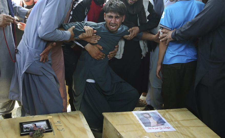 FILE - In this Aug. 18, 2019 file photo, men hold back a grieving relative next to the coffins of victims of a wedding hall bombing during a mass funeral in Kabul, Afghanistan. A new survey released by the Asia Foundation Tuesday, Dec. 3, 2019, says Afghans are increasingly fearful for their personal safety, but slightly more believe their war-weary country is moving in the right direction compared to previous years. (AP Photo/Rafiq Maqbool, File)
