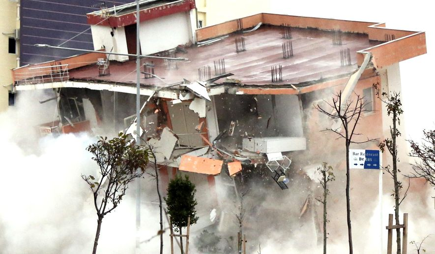 The Albanian army uses a remote-controlled explosion to demolish a building in the western port city of Durres, Albania, Tuesday, Dec. 3, 2019. A remote-controlled explosion has demolished the six-storied building considered threatening after being damaged from the 6.4 magnitude earthquake in Albania. A quake a week ago killed 51 persons, injured more than 3,000 people, and damaged more than 11,000 buildings. (AP Photo/Hektor Pustina)