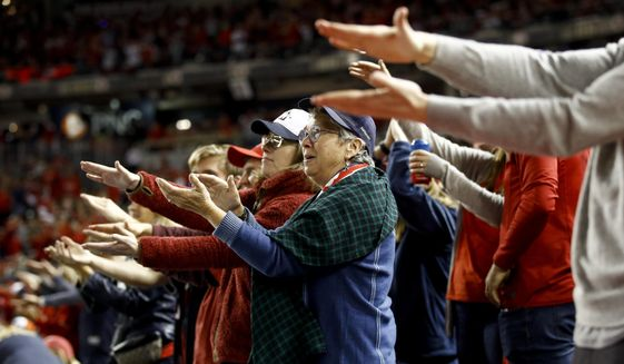"""FILE - In this Oct. 25, 2019, file photo, fans gesture the baby shark as Washington Nationals' Gerardo Parra bats during the sixth inning of Game 3 of the baseball World Series against the Houston Astros, in Washington. Creators of the viral video """"Baby Shark,"""" whose """"doo doo doo"""" song was played at the World Series in October, are developing a version in Navajo. (AP Photo/Patrick Semansky, File)"""