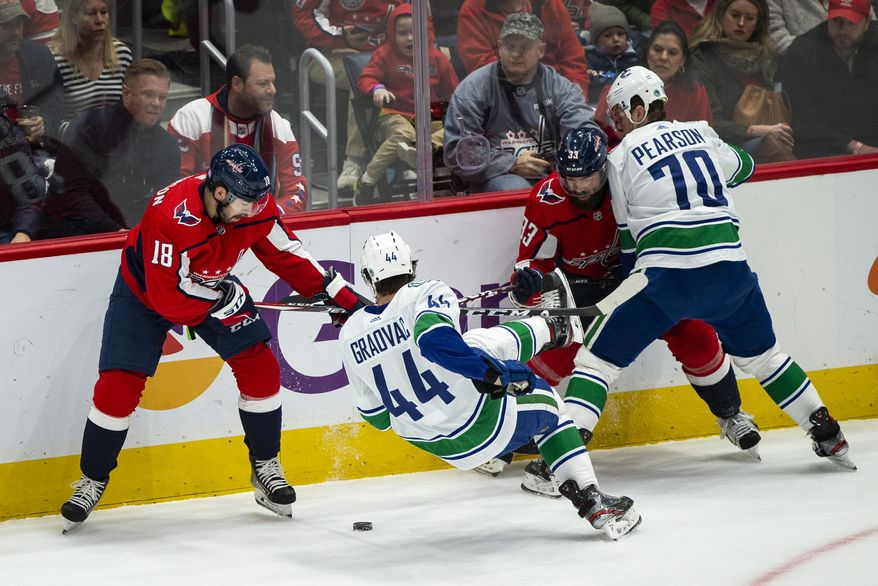 Washington Capitals center Chandler Stephenson (18), and defenseman Radko Gudas (33), from the Czech Republic, guard against Vancouver Canucks center Tyler Graovac (44) and left wing Tanner Pearson (70) during the first period of an NHL hockey game, Saturday, Nov. 23, 2019, in Washington. (AP Photo/Al Drago)