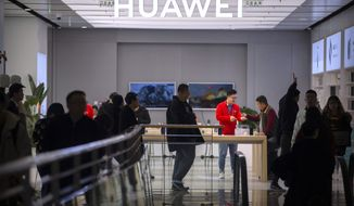 In this Nov. 20, 2019, photo, customers shop at a Huawei store at a shopping mall in Beijing. The founder of Huawei says the Chinese tech giant is moving its U.S. research center to Canada due to American restrictions on its activities. (AP Photo/Mark Schiefelbein)