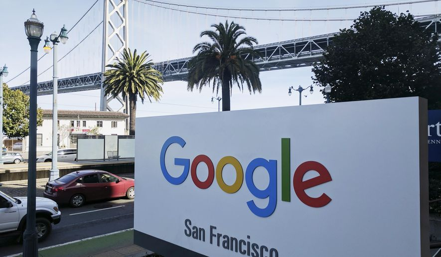 FILE - In this Oct. 31, 2018, file photo shows signage outside the offices of Google in San Francisco with the San Francisco-Oakland Bay Bridge in the background. Four workers fired from Google in November 2019 are planning to file charges against the company with a federal agency. They are claiming the company unfairly retaliated against them for organizing workers around social causes. (AP Photo/Michael Liedtke, File)
