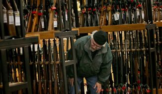 In this Nov. 29, 2019, file photo, a man looks at the shotgun section of Cabela's while shopping on Black Friday in Hazelwood, Mo. (Christian Gooden/St. Louis Post-Dispatch via AP) ** FILE **