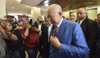 Former Malaysian Prime Minister Najib Razak, center, walks out from the courtroom at the court house in Kuala Lumpur, Malaysia for his corruption trial Tuesday, Dec. 3, 2019. Razak has started his defense Tuesday, Dec. 3, 2019, in his first corruption trial linked to the multibillion-dollar looting of the 1MDB state investment fund, that helped led to his downfall last year. (AP Photo)