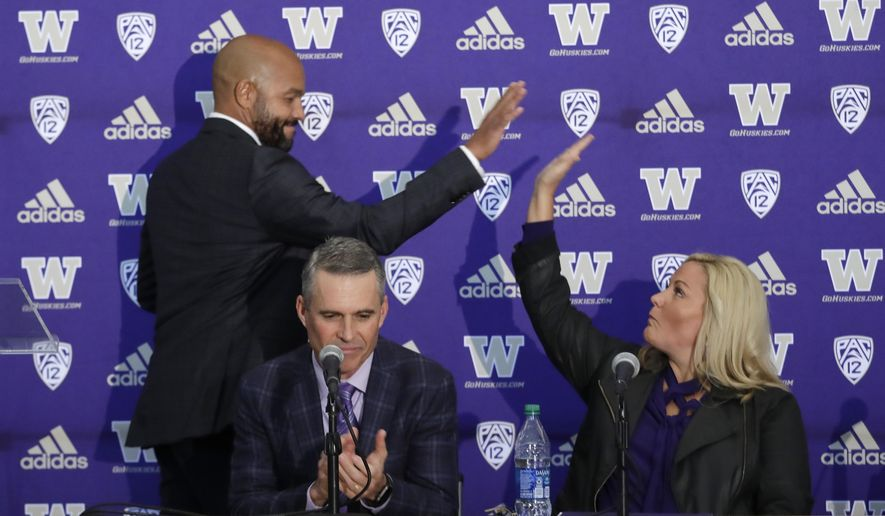 Washington NCAA college football head coach Chris Petersen, center, applauds as defensive coordinator Jimmy Lake, left, high-fives athletic director Jen Cohen after speaking during a news conference about Petersen's decision to resign and Lake taking over his job, Tuesday, Dec. 3, 2019, in Seattle. Petersen unexpectedly resigned on Monday, a shocking announcement with the Huskies coming off a 7-5 regular season and bound for a sixth straight bowl game under his leadership. Petersen will coach Washington in a bowl game, his final game in charge. (AP Photo/Elaine Thompson)