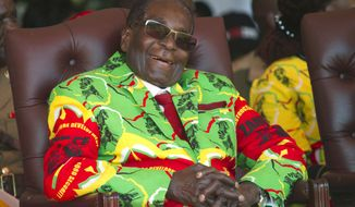 FILE - In this Friday, June, 2, 2017 file photo Zimbabwean President Robert Mugabe smiles during a youth rally in Marondera, east of Harare. The wealth of Zimbabwe's former longtime president Robert Mugabe was long a mystery. Now the first official list of assets to be made public says he left behind $10 million and several houses when he died in September, 2019. Some in Zimbabwe view that estate as far too modest for Mugabe, who ruled for 37 years and was accused by critics of accumulating vast riches and presiding over grand corruption. (AP Photo/Tsvangirayi Mukwazhi, File)