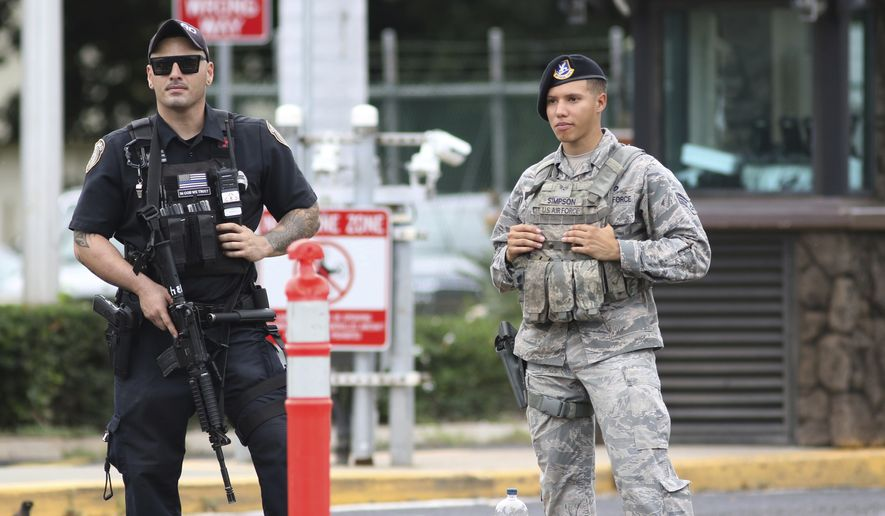 Security stands guard outside the main gate at Joint Base Pearl Harbor-Hickam, in Hawaii, Wednesday, Dec. 4, 2019. A shooting at Pearl Harbor Naval Shipyard in Hawaii left at least one person injured Wednesday, military and hospital officials said. Joint Base Pearl Harbor-Hickam spokesman Charles Anthony confirmed that there was an active shooting at Pearl Harbor Naval Shipyard. (AP Photo/Caleb Jones)