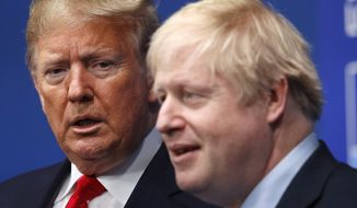 British Prime Minister Boris Johnson, right, and U.S. President Donald Trump pose during a group photo during a NATO leaders meeting at The Grove hotel and resort in Watford, Hertfordshire, England, Wednesday, Dec. 4, 2019. NATO Secretary-General Jens Stoltenberg rejected Wednesday French criticism that the military alliance is suffering from brain death, and insisted that the organization is adapting to modern challenges. (Peter Nicholls, Pool Photo via AP)