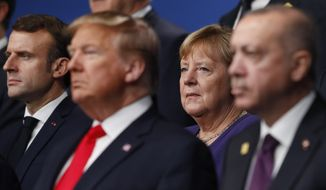 From left, French President Emmanuel Macron, U.S. President Donald Trump, German Chancellor Angela Merkel and Turkish President Recep Tayyip Erdogan pose during a group photo for a NATO leaders meeting at The Grove hotel and resort in Watford, Hertfordshire, England, Wednesday, Dec. 4, 2019. NATO Secretary-General Jens Stoltenberg rejected Wednesday French criticism that the military alliance is suffering from brain death, and insisted that the organization is adapting to modern challenges. (Peter Nicholls, Pool Photo via AP)