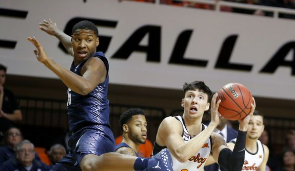Oklahoma State's Lindy Waters III (21) attempts a shot beside Georgetown's Myron Gardner (15) during an NCAA college basketball game Wednesday, Dec. 4, 2019, in Stillwater, Okla. (Bryan Terry/The Oklahoman via AP) ** FILE **