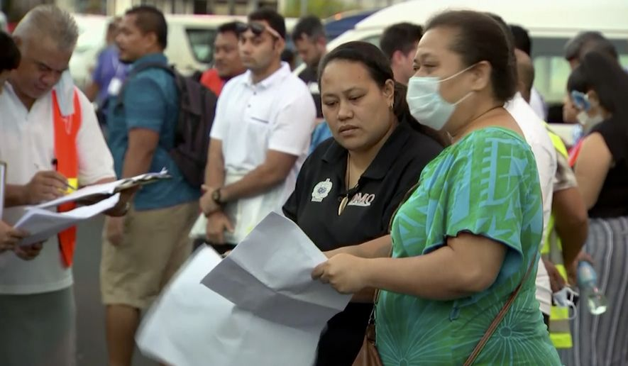 In this image from video,  people gather outside a health emergency operation center Thursday, Dec. 5, 2019, in Apia, Samoa.  Samoas main streets were eerily quiet on Thursday, Dec. 5, 2019, as the government stepped up efforts to curb a measles epidemic that has killed 62 people. (TVNZ via AP)