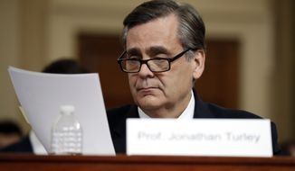 George Washington University Law School professor Jonathan Turley reviews papers as he testifies during a hearing before the House Judiciary Committee on the constitutional grounds for the impeachment of President Donald Trump, Wednesday, Dec. 4, 2019, on Capitol Hill in Washington. (AP Photo/Jacquelyn Martin)