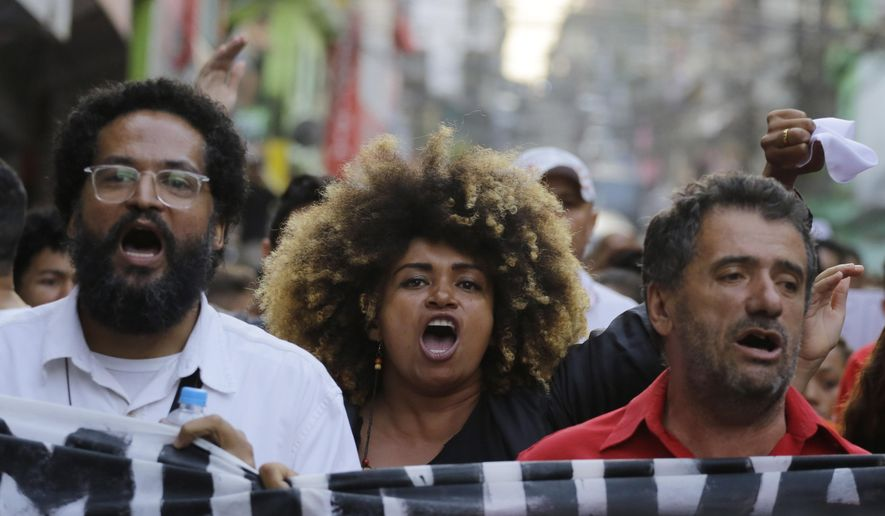 Residents of the Paraisopolis slum take part in a demonstration asking for peace, in Sao Paulo, Brazil, Wednesday, Dec. 4, 2019. Police officers pursuing fleeing suspects clashed with people at a street party in the Sao Paulo slum on Sunday, setting off a stampede in which nine people died. (AP Photo/Nelson Antoine)