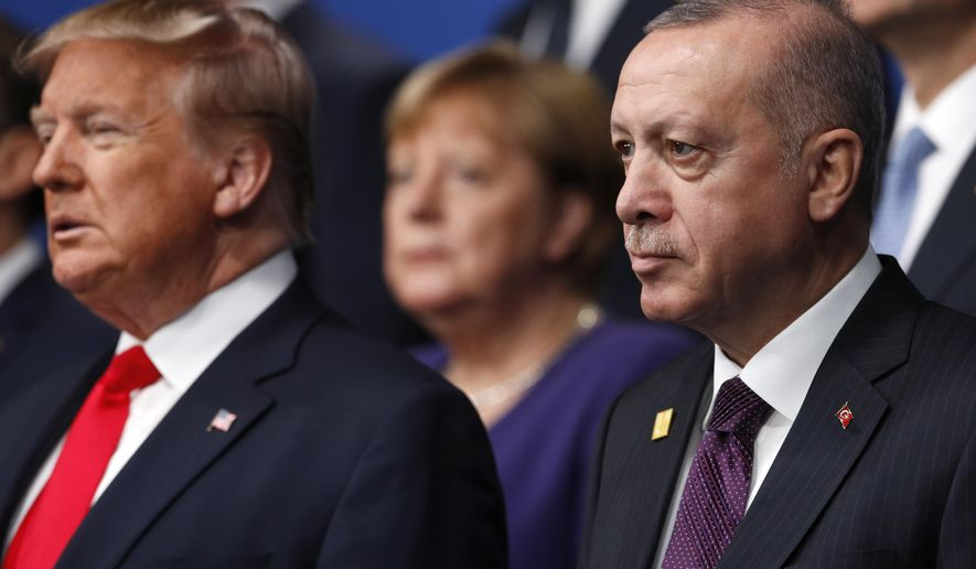 From left, U.S. President Donald Trump, German Chancellor Angela Merkel and Turkish President Recep Tayyip Erdogan pose during a group photo for a NATO leaders meeting at The Grove hotel and resort in Watford, Hertfordshire, England, Wednesday, Dec. 4, 2019. (Peter Nicholls, Pool Photo via AP) **FILE**
