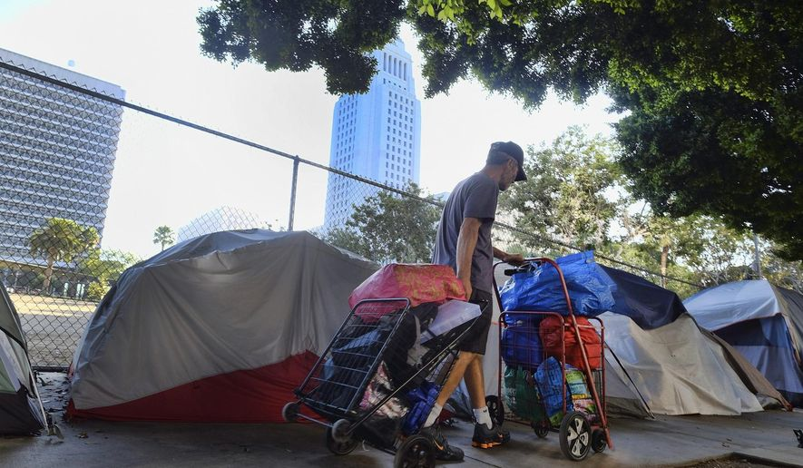 FILE - In this Monday, July 1, 2019 file photo, a homeless man moves his belongings from a street behind Los Angeles City Hall as crews prepared to clean the area. California Gov. Gavin Newsom blamed the Trump administration on Wednesday, Dec. 4, 2019, for withholding data that is blocking the release of $650 million aid to combat homelessness. (AP Photo/Richard Vogel, File)