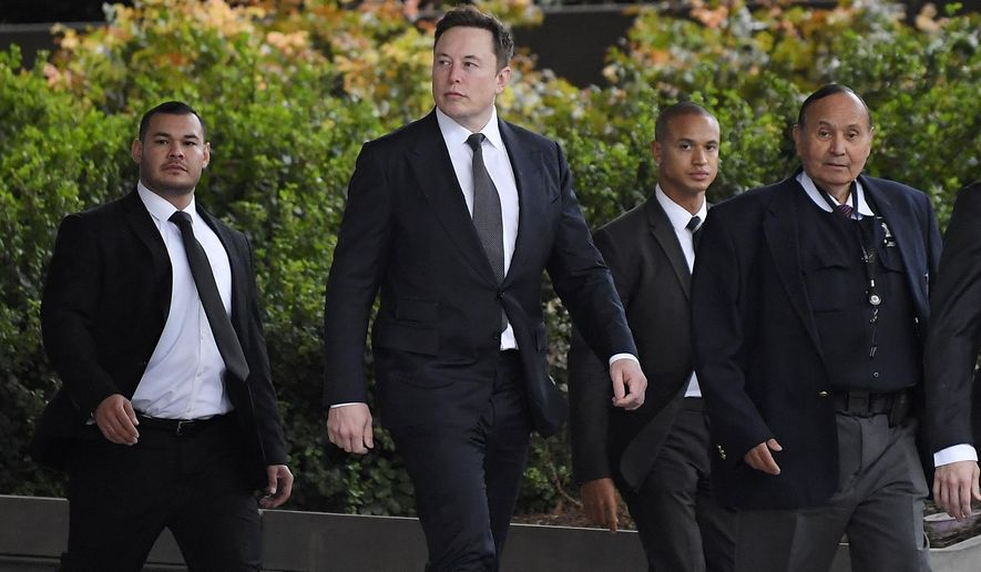 Tesla CEO Elon Musk, second from left, arrives at U.S. District Court Wednesday, Dec. 4, 2019, in Los Angeles. Musk is going on trial for his troublesome tweets in a case pitting the billionaire against a British diver he allegedly dubbed a pedophile. (AP Photo/Mark J. Terrill)