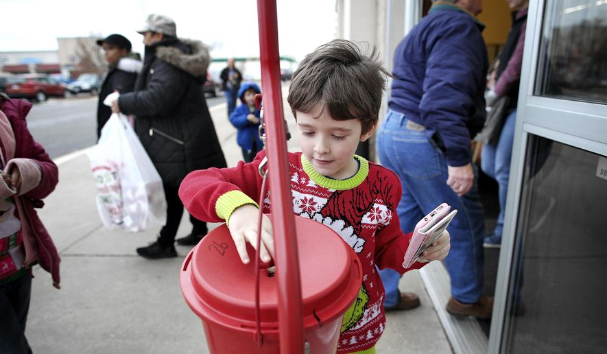 Cameron Bray donates to the the Salvation Army outside of Hobby Lobby in Janesville, Wisconsin, on Saturday, Nov. 29, 2019. Bell ringer Debi Pulver averaged $63 raised per hour while ringing the ball last year. (Anthony Wahl/The Janesville Gazette via AP) **FILE**