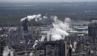 FILE - In this March 8, 2018, file photo wetlands are seen beyond the Shell Norco refinery in Norco, La. The world may be heading into an oversupply of oil, and that possibility is hanging over members of the OPEC cartel, which will meet later this week to decide whether to further cut production to boost prices. (AP Photo/Gerald Herbert, File)