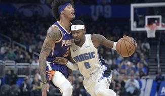 Orlando Magic guard Terrence Ross (8) drives to the basket in front of Phoenix Suns forward Kelly Oubre Jr. (3) during the first half of an NBA basketball game Wednesday, Dec. 4, 2019, in Orlando, Fla. (AP Photo/Phelan M. Ebenhack)