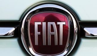 FILE - In this Oct. 31, 2019 file photo, a Fiat logo is pictured on a car in Bayonne, southwestern France. Union leaders from Fiat Chrysler factories are sending a new four-year contract to a membership vote. (AP Photo/Bob Edme, File)