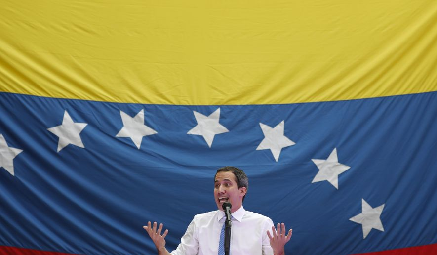 FILE - In this Sept. 30, 2019 file photo, opposition leader and self-proclaimed interim President Juan Guaido speaks during a citizen assembly at a square in the neighborhood of El Paradiso in Caracas, Venezuela. On Tuesday, Dec. 3, 2019, the opposition-controlled National Assembly at the last minute scratched a schedule debate on a $350 million credit from a regional development bank to address an electricity emergency that has left much of western Venezuela in the dark from blackouts for months. (AP Photo/Ariana Cubillos, File)
