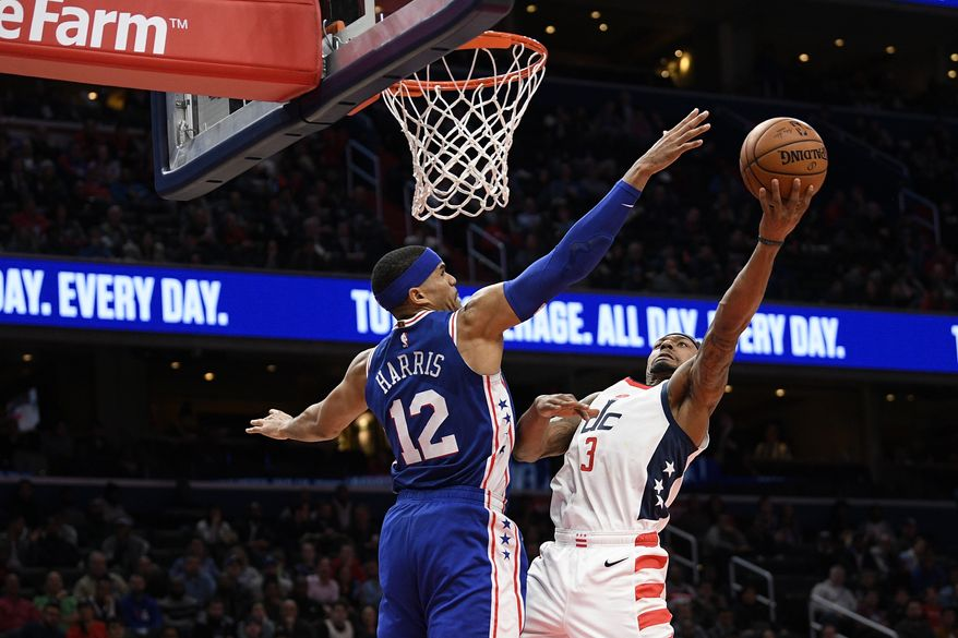 Washington Wizards guard Bradley Beal (3) goes to the basket as he is defended by Philadelphia 76ers forward Tobias Harris (12) during the second half of an NBA basketball game, Thursday, Dec. 5, 2019, in Washington. The Wizards won 119-113. (AP Photo/Nick Wass)