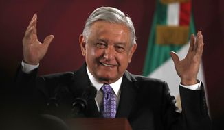 Mexican President Andres Manuel Lopez Obrador smiles during his daily morning press conference at the National Palace in Mexico City, Wednesday, Nov. 13, 2019. Mexico has granted asylum to Bolivia's former President Evo Morales, who resigned on Nov. 10th under mounting pressure from the military and the public after his re-election victory triggered weeks of fraud allegations and deadly protests. (AP Photo/Marco Ugarte)
