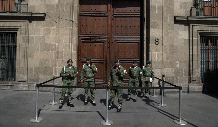 Military police stand guard outside an entrance to the National Palace during a private meeting between U.S. Attorney General William Barr and Mexico's President Andres Manuel Lopez Obrador, in Mexico City, Thursday, Dec. 5, 2019. (AP Photo/Rebecca Blackwell)