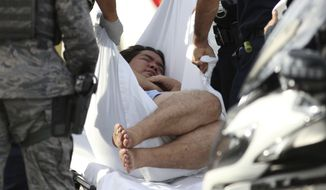 An unidentified male is taken away on a stretcher outside the main gate at Joint Base Pearl Harbor-Hickam, Wednesday, Dec. 4, 2019, in Hawaii, following a shooting. (AP Photo/Caleb Jones)