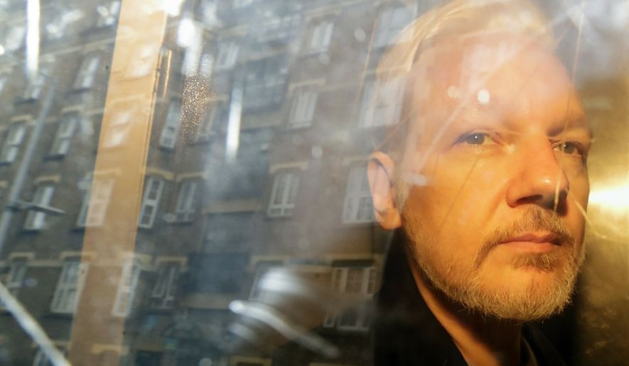 Buildings are reflected in the window of a car as WikiLeaks founder Julian Assange is taken from court, where he appeared on charges of jumping British bail seven years ago, in London on May 1, 2019. (AP Photo/Matt Dunham)