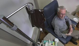 In this Nov. 22, 2019, photo, Charles Flagg, who is stricken with Alzheimer's disease, receives the contents of an intravenous bag while participating in a study on the drug Aducanumab at Butler Hospital in Providence, R.I. New results were released on the experimental medicine whose maker claims it can slow the decline of Alzheimer's disease, the most common form of dementia. (AP Photo/Charles Krupa)