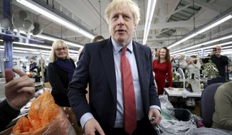 Britain's Prime Minister Boris Johnson visits John Smedley Mill in Matlock, England, Thursday, Dec. 5, 2019. Britain is holding a general election a week from now and fractures are emerging within jittery political parties unsure how a volatile electorate will judge them. Conservative Prime Minister Boris Johnson and main opposition Labour Party leader Jeremy Corbyn both faced criticism of their moral character. (Hannah McKay/Pool Photo via AP)